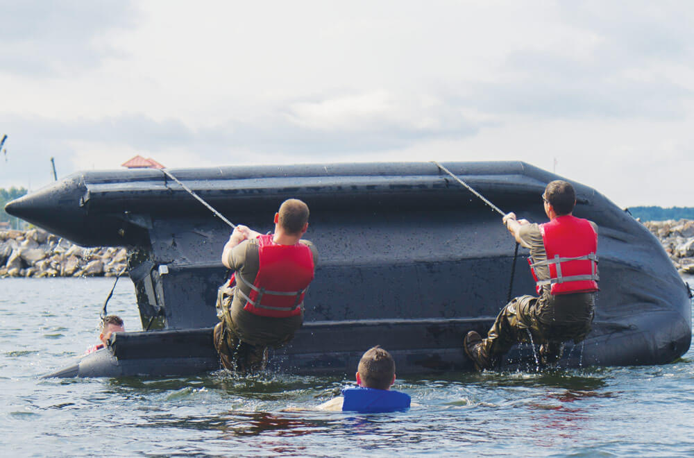 Army National Guard Soldiers with Charlie Troop, 1st Squadron, 172nd Cavalry Regiment (Mountain), 86th Infantry Brigade Combat Team (Mountain), and Vermont Army National Guard right a zodiac boat during boat during boat capsizing training in Burlington, Vt.