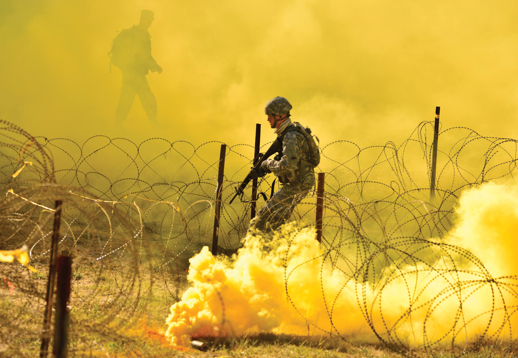 An Oregon Army National Guard Soldier proceeds through a combination of thick smoke, tear gas and razor wire as their unit mentor watches from above, during the 2017 Oregon Best Warrior Competition at Camp Rilea, near Warrenton, Ore. Soldiers compete in a variety of warrior tasks to determine which Soldier and NCO will represent Oregon at the regional-level competition.