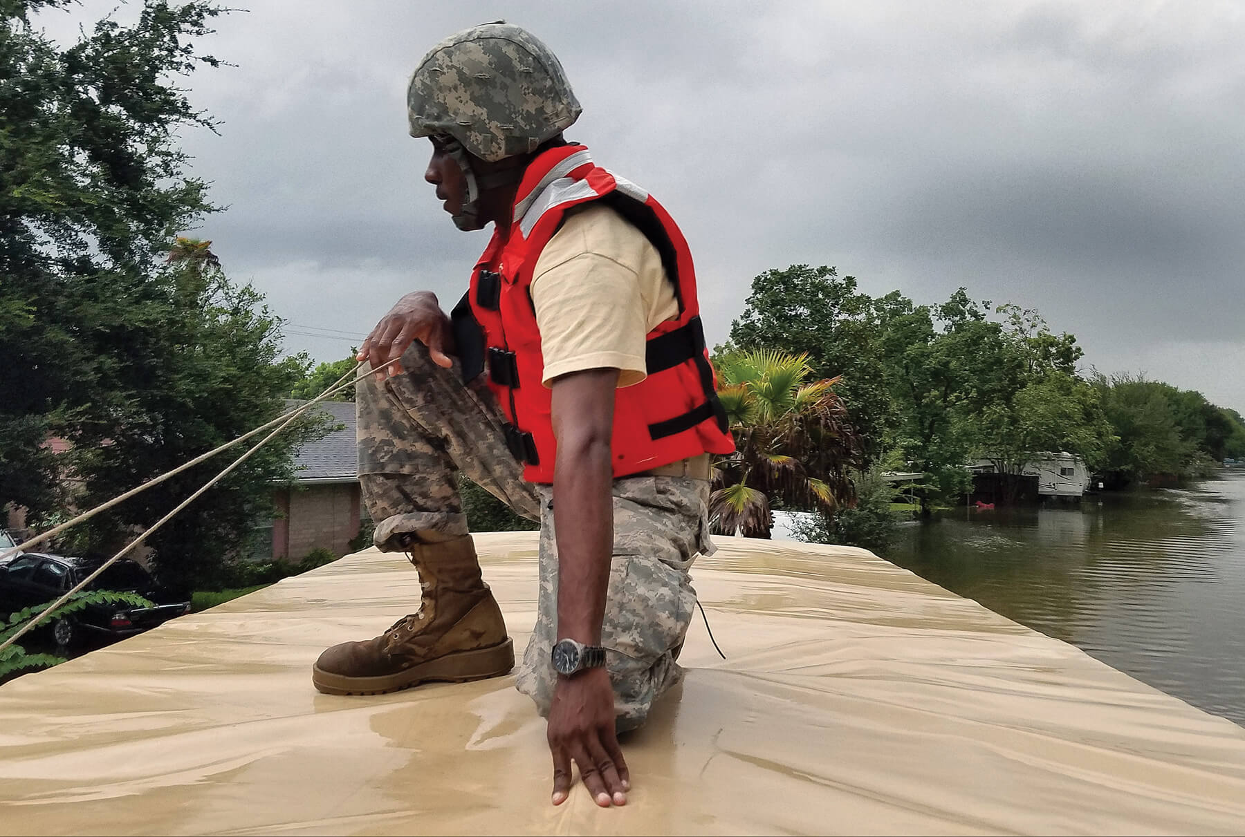 A Soldier With The Texas Army National Guard keeps an eye on rising floodwaters in a Houston neighborhood while working to rescue those stranded by Hurricane Harvey. More than 12,000 members of the Texas National Guard were called out to support local authorities in response to the storm.