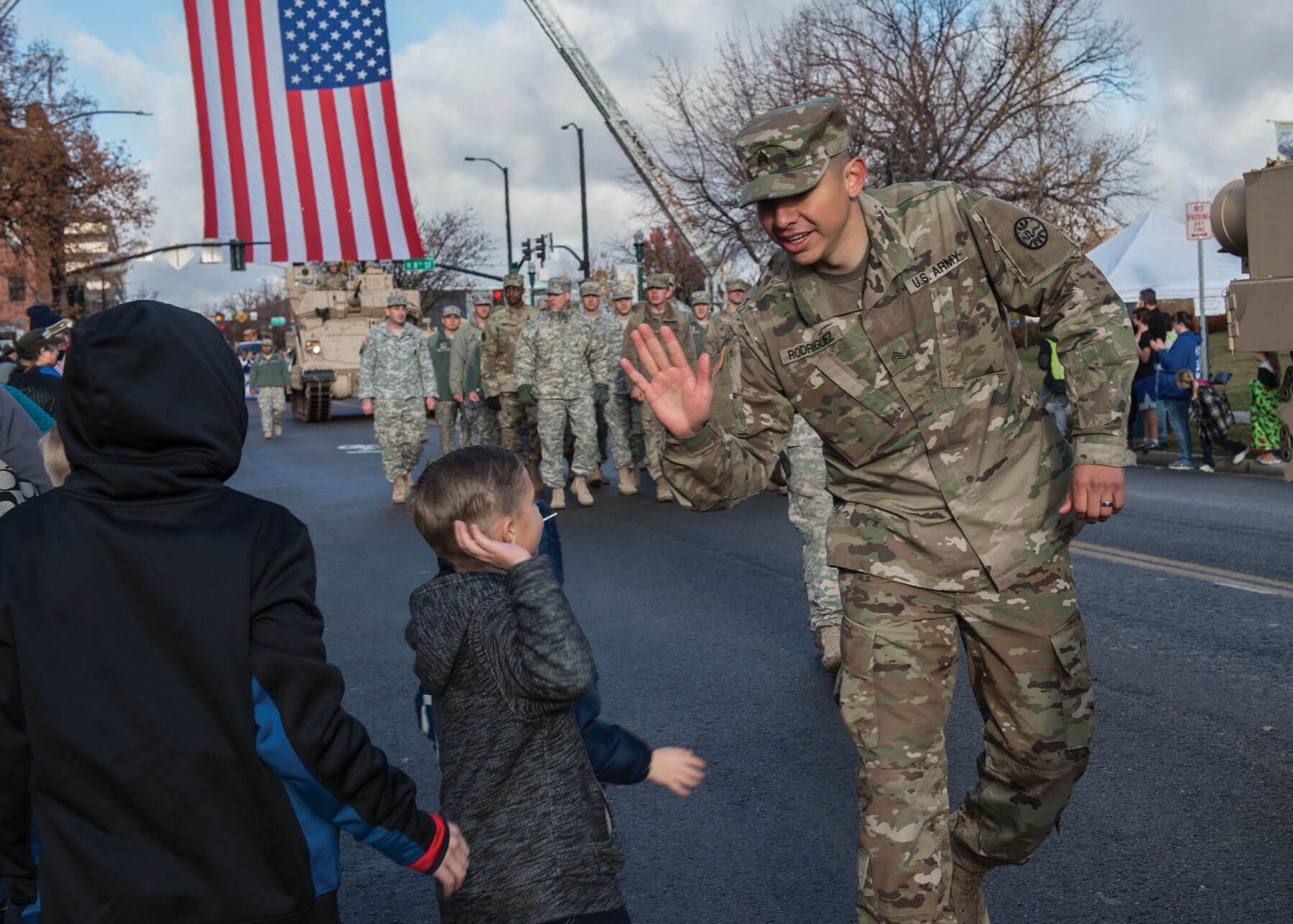 "A Soldier from the Idaho National Guard at Gowen Field, ""high-fives"" a young spectator while participating in the 2017 Boise Veterans Day Parade in downtown Boise, Idaho. The parade theme was ""Saluting the Rich Military History of Gowen Field."""