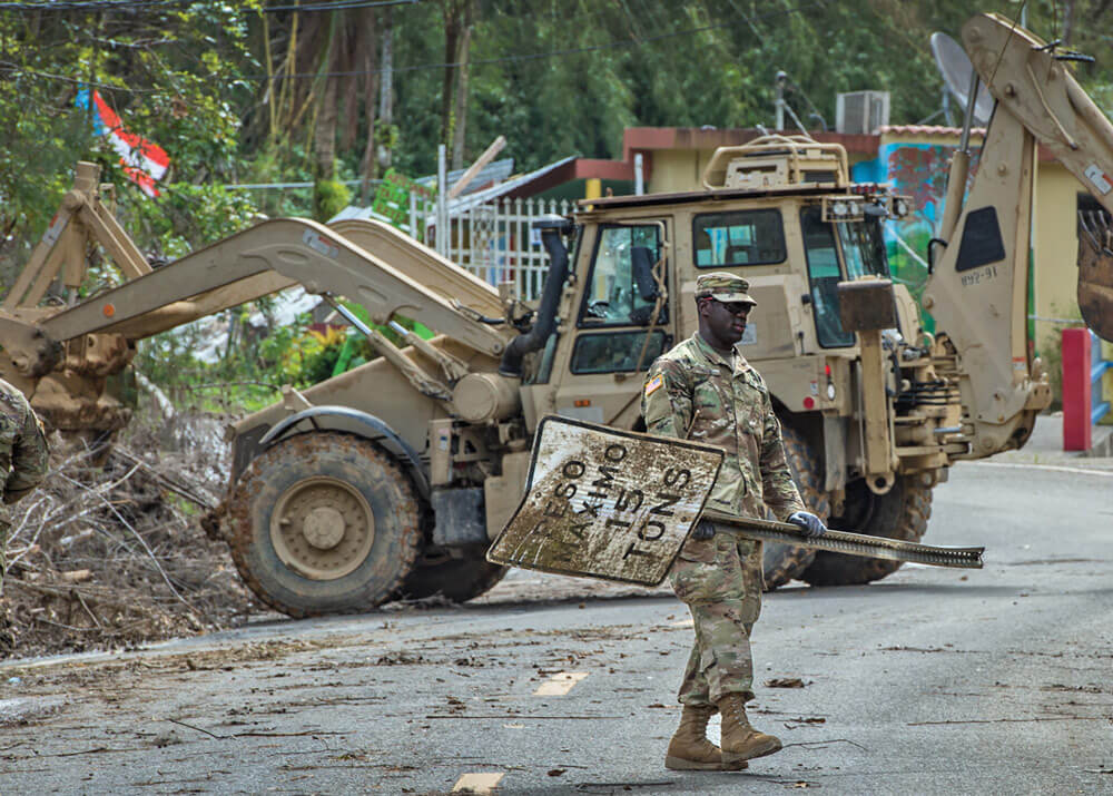 PFC Raiquan Wade of Charleston, South Carolina helps clear debris from the roads near Cayey, Puerto Rico in the aftermath of Hurricane Maria.