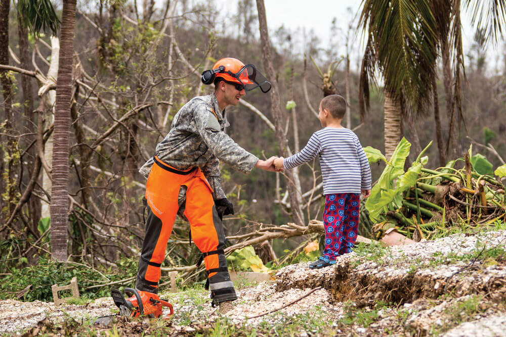 SPC Raymond Avery of Townville, South Carolina takes a break from clearing roads in Puerto Rico to say hello to a young boy in the vicinity of Cayey.