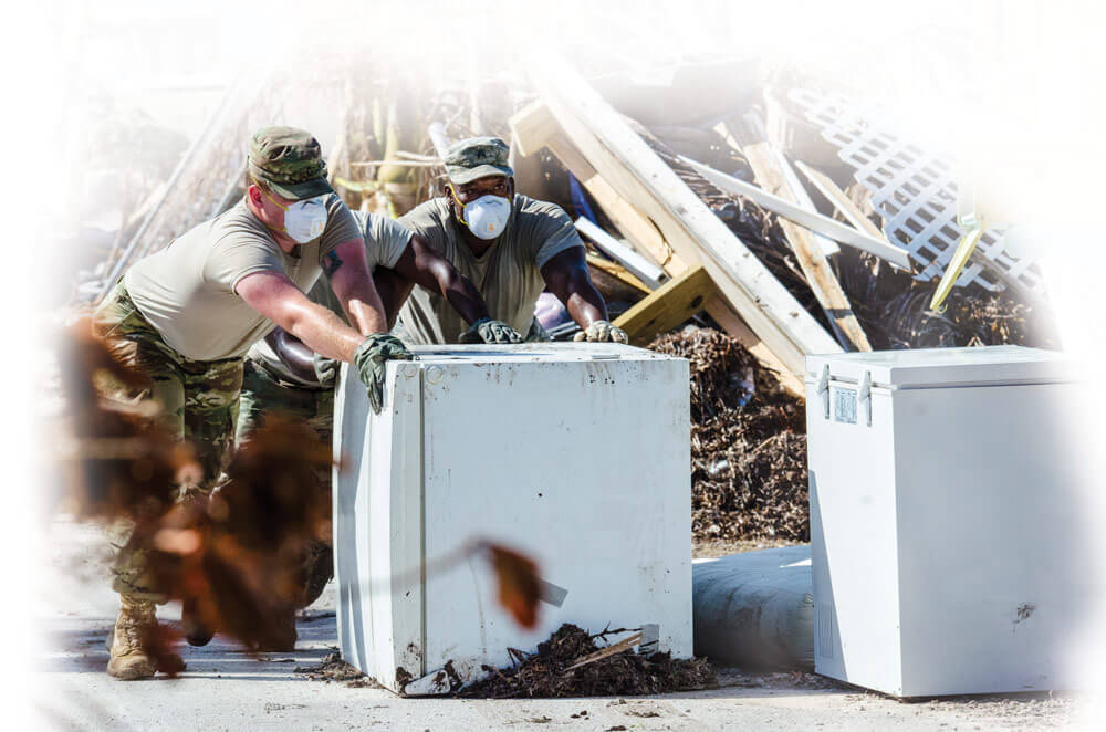Army PFC Cody Hughes (left) and team leader SGT Robert Brown with the 753rd Brigade Engineer Battalion's Company B remove a refrigerator with weeks- old food from a Marathon, Fla., home left devastated by Hurricane Irma.