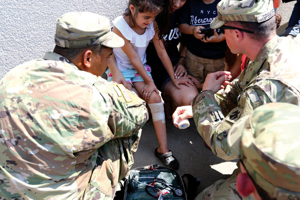 PFC Mykalob Stephens and members of Oklahoma National Guard's Company D, 1st Battalion, 179th Infantry Regiment, 45th Infantry Division, bandage minor wounds received by residents during Hurricane Harvey in Port Arthur, Texas.