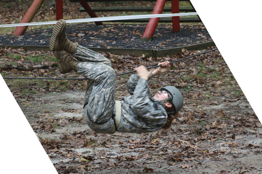 A Cadet moves through the ropes section of a team development obstacle course.