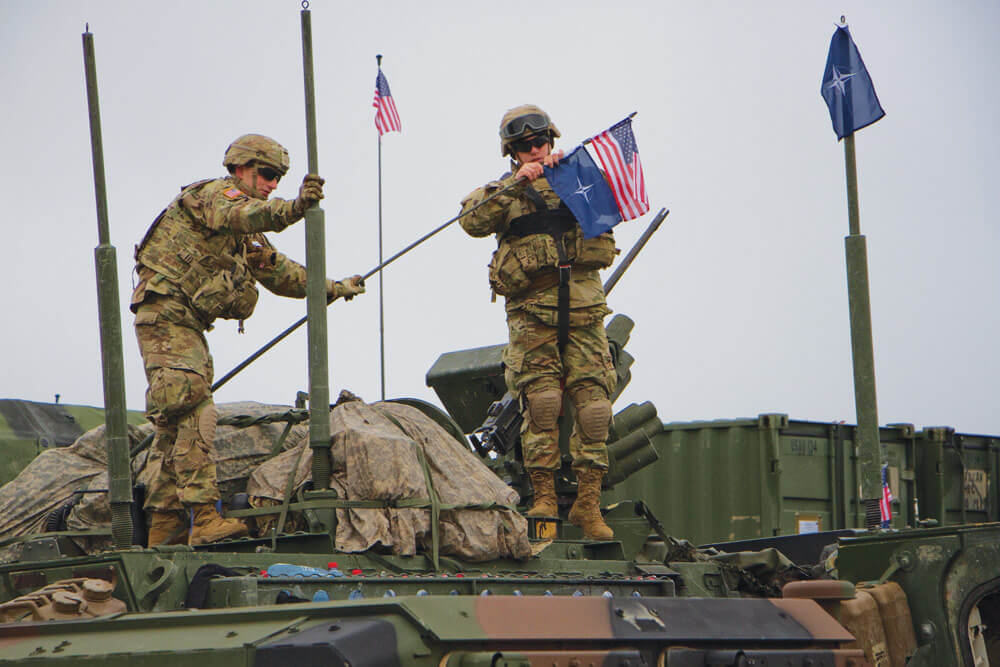 Soldiers assigned to 3rd Squadron, 2nd Cavalry Regiment place U.S. and NATO flags on the antenna of their Stryker Combat Vehicle.