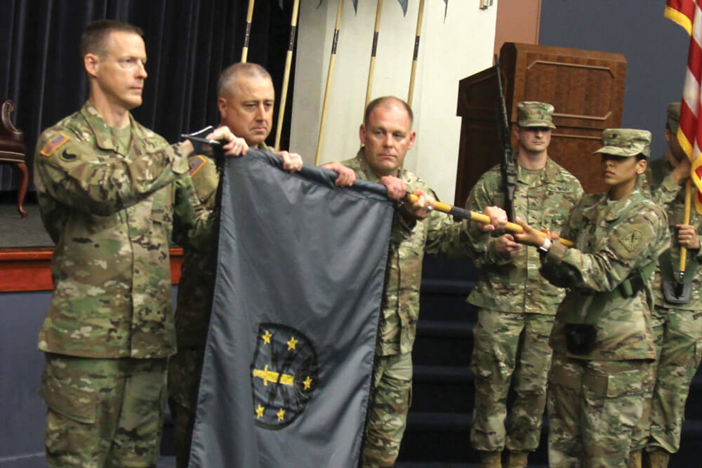 The command team for the 91st Cyber Brigade uncases their new unit colors.