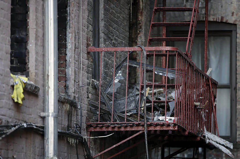 Charred items sit on the burnt-out fire escape of the New York City apartment building where PFC Emmanuel Mensah saved the lives of four people during a deadly fire that broke out in the building on Friday, Dec. 29, 2017. AP Photo by Julio Cortez.