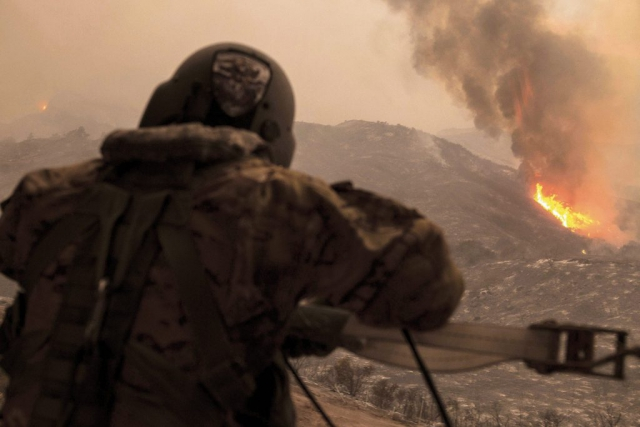 SGT Anthony Orduno, a UH-60 Black Hawk helicopter crew chief for the California Army National Guard, takes stock of the Thomas Fire as he and the rest of the Black Hawk crew spend the day fighting the blaze on Dec. 9, 2017. At the time, 30 helicopters, 575 engines and 3,993 people from various organizations were fighting the flames. The Thomas Fire would go on to burn more acres than any fire in modern California history. California National Guard photo by SrA Crystal Housman.