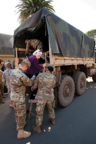 Soldiers from the California National Guard's 1114th Composite Transportation Company help a 90-year-old woman climb up a ladder and into the back of their light medium tactical vehicle (LMTV) after evacuating the woman from her Montecito, Calif., neighborhood to a centralized drop-off point, Jan. 11, 2018. Massive mudslides left the community in ruins after soil-stabilizing vegetation was destroyed by the Thomas Fire. Heavy rains followed the blaze and caused mudslides that destroyed 73 buildings, damaged 466 buildings and killed at least 17 people. California National Guard photo by SrA Crystal Housman.