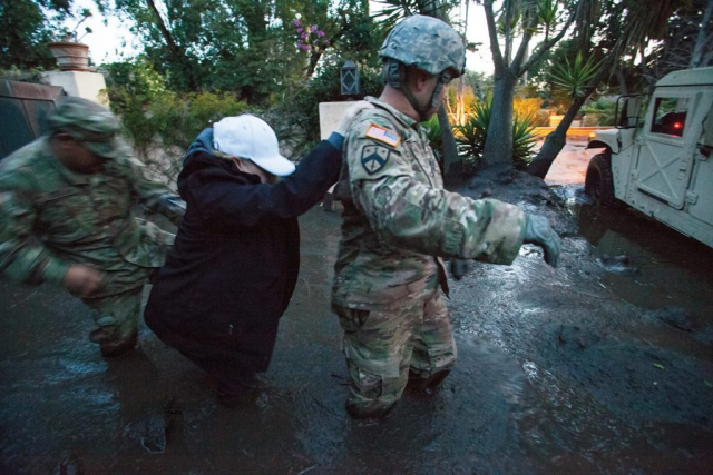 SGT Jose Paiz (right) and SSG Michael Aguilar both of the 1114th Composite Truck Company, California Army National Guard, guide a resident through thick, knee-deep mud from a Montecito, Calif., home to the Soldiers' HMMWV. The 1114th is credited with rescuing or evacuating more than 1,800 citizens in the Montecito area following the deadly mudslide that struck the city in the predawn hours of Jan. 9, 2018. California National Guard photo by SrA Crystal Housman.