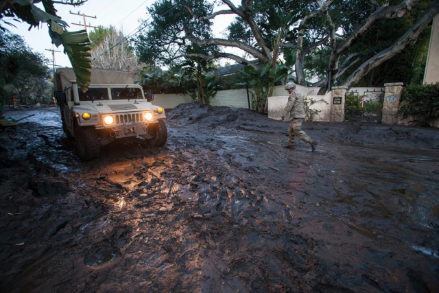 SGT Jose Paiz of the 1114th Composite Truck Company, California National Guard, walks back to a HMMWV, Jan. 12, 2018, after checking the depth of mud further down the street during a rescue mission in Montecito, Calif. California National Guard photo by SrA Crystal Housman.