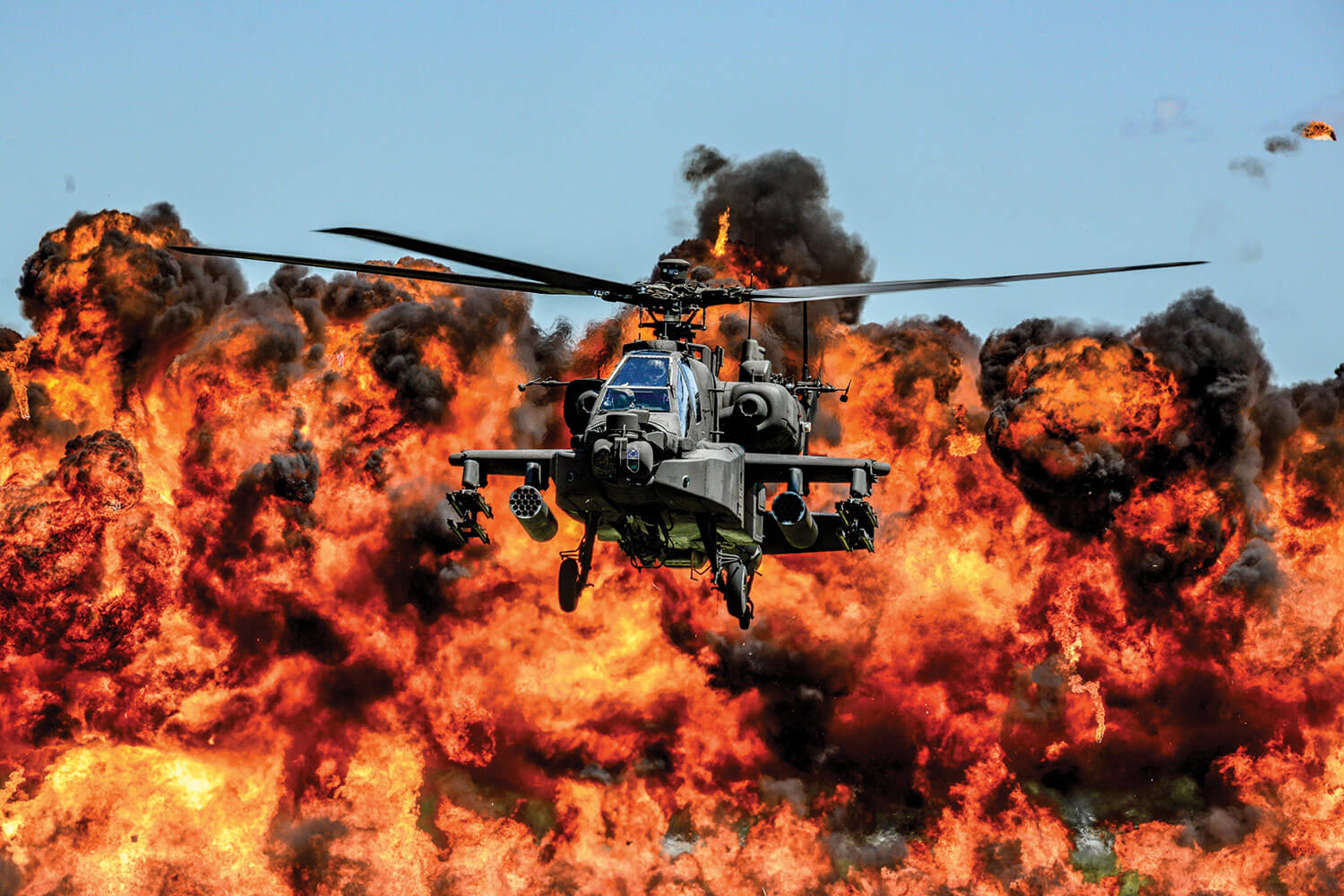 An AH-64D Apache Attack Helicopter, assigned to the 1-151st Attack Reconnaissance Battalion, flies in front of a wall of fire during the South Carolina National Guard Air and Ground Expo at McEntire Joint National Guard Base, S.C., May 6, 2017. The expo is a combined arms demonstration that showcases the abilities of South Carolina National Guard members. It also offers opportunities for the South Carolina Guard to express its thanks for the support shown by fellow South Carolinians in the surrounding community. South Carolina National Guard photo by Tech Sgt Jorge Intriago.
