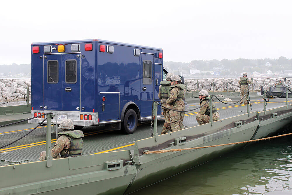 Soldiers from the 1437th Multi-Role Bridge Company guide an ambulance and crew from the 51st Civil Support Team to a designated area before maneuvering the 130-foot ribbon bridge into the waters of the Straits of Mackinac. Michigan National Guard photo by Scott Martzke.