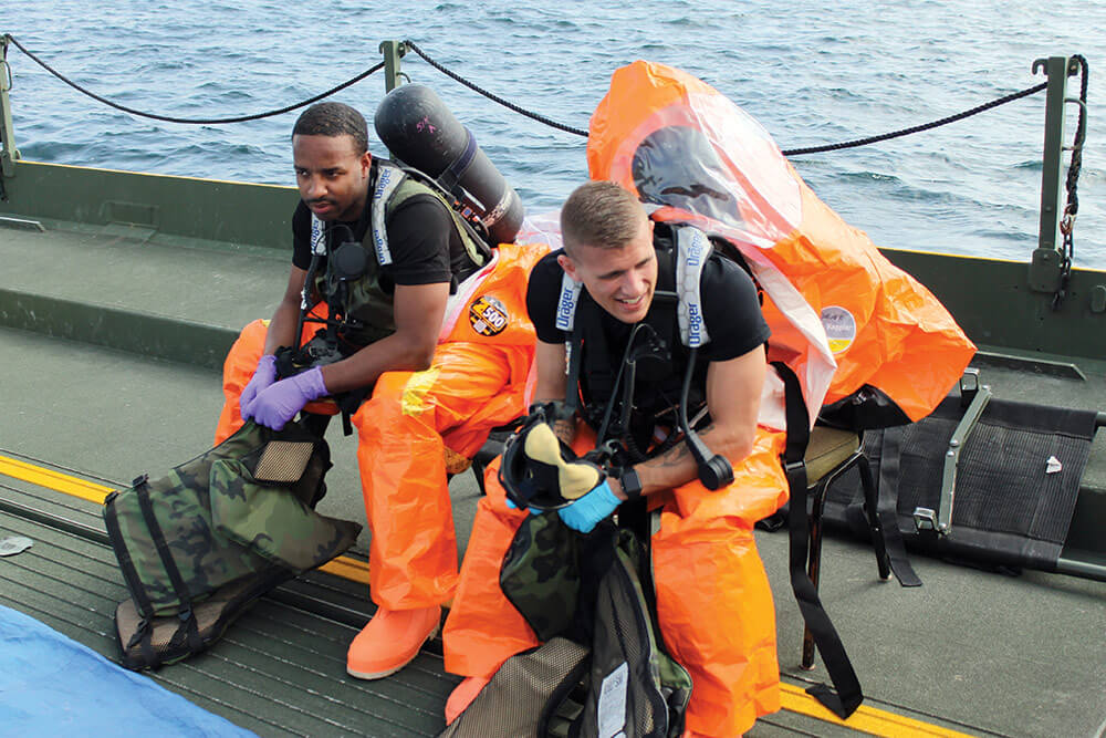 Seated aboard a Shepler's Ferry® boat, SGT JaBerry Smith (left), survey team member, Michigan National Guard, and SGT Riley Turner, survey team member, 52nd Civil Support Team, Ohio National Guard, prepare for entry into a simulated hot zone. Michigan National Guard photo by Scott Martzke