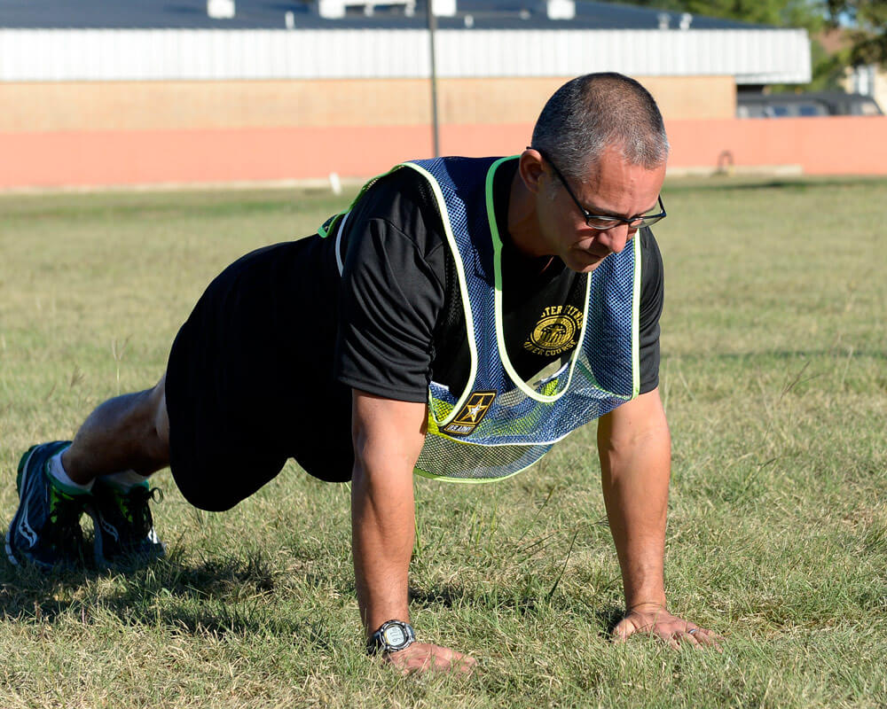Texas Army National Guard SSG Anthony Delagarza, a Master Fitness Trainer Course instructor, demonstrates a correct push-up on the parade field at Camp Mabry in Austin, Texas.
