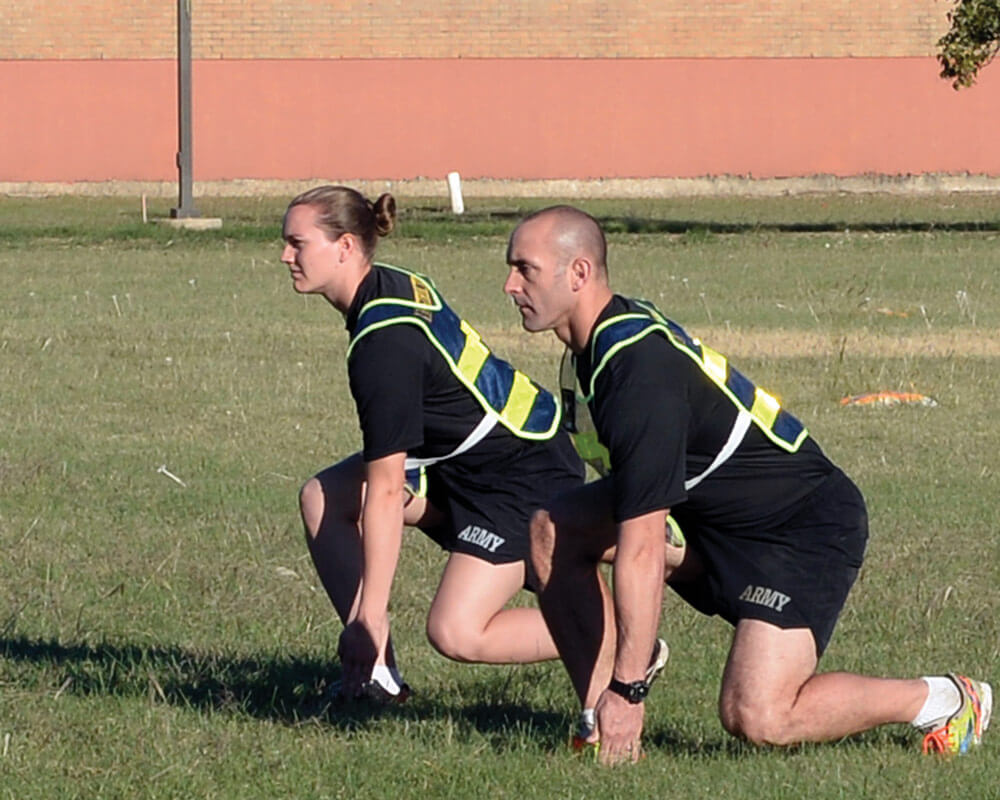 Master Fitness Trainer Course instructors SSG Sara Elkins and SFC Athan Schindler demonstrate shuttle runs during a round of exercises on the parade field at Camp Mabry as part of the Master Fitness Trainer Course.
