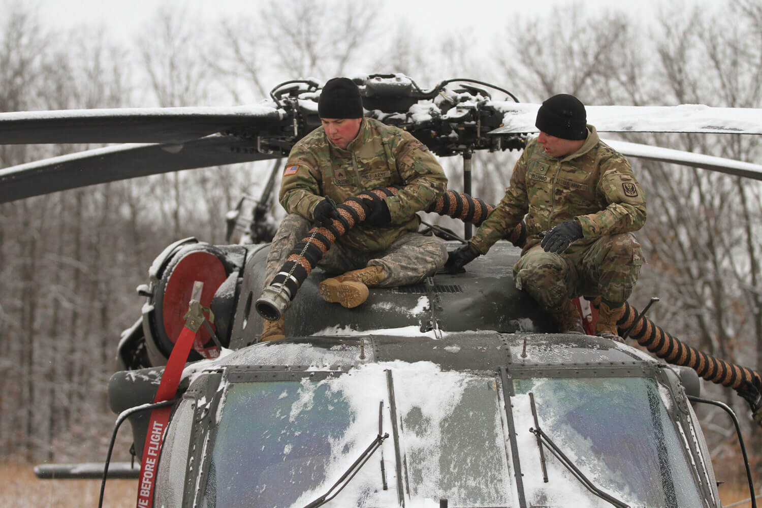 Two Missouri Army National Guard UH-60 helicopter mechanics, SGT Christopher Parsons (left) and PFC Austin Villhard from Detachment 1, Company D, 1-106th Aviation, defrost a UH-60 Black Hawk helicopter during an Annual Training exercise at Camp Clark, in Nevada, Mo. Missouri Army National Guard photo by SGT Emily Finn