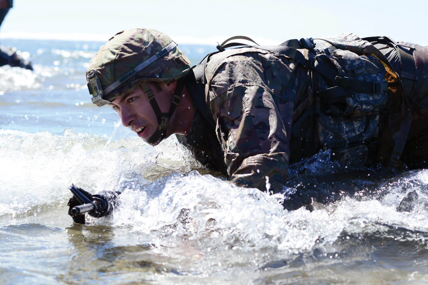 Oregon Army National Guard SGT Dane Moorehead, with B Troop, 1st Squadron, 82nd Cavalry Regiment, 82nd Brigade Troop Command, high-crawls to the shore, through the surf in full battle gear during the Omaha Beach event at the 2017 Oregon Best Warrior Competition held at Camp Rilea, near Warrenton, Oregon. Moorehead is the 2017 Noncommissioned Officer of the Year. Oregon Army National Guard photo by SFC April Davis