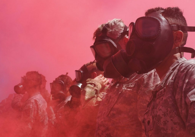 Arizona Army National Guard Soldiers from the 2220th Transportation Company are engulfed by colored smoke after putting on their protective masks during a simulated chemical attack at Florence Military Reservation in Florence, Ariz. Arizona Army National Guard photo by SSG Brian A. Barbour