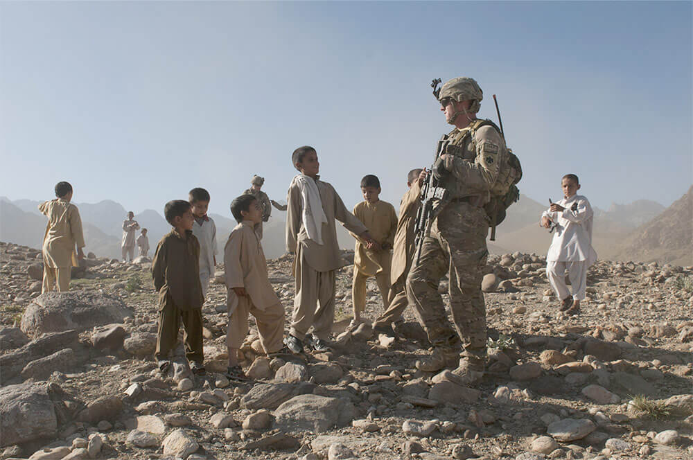 A Soldier of the 45th Infantry Brigade Combat Team interacts with children from a local Afghan village. Oklahoma Army National Guard photo by SPC Leslie Goble