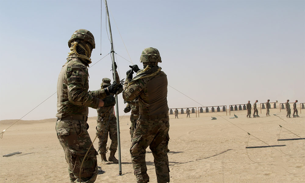 Soldiers assigned to the 35th Infantry Division hoist a field communication antenna while at the rifle range during Operation Blaze the Trail, a training exercise held at Camp Buehring, Kuwait. U.S. Army photo by SSG Jeremy Miller