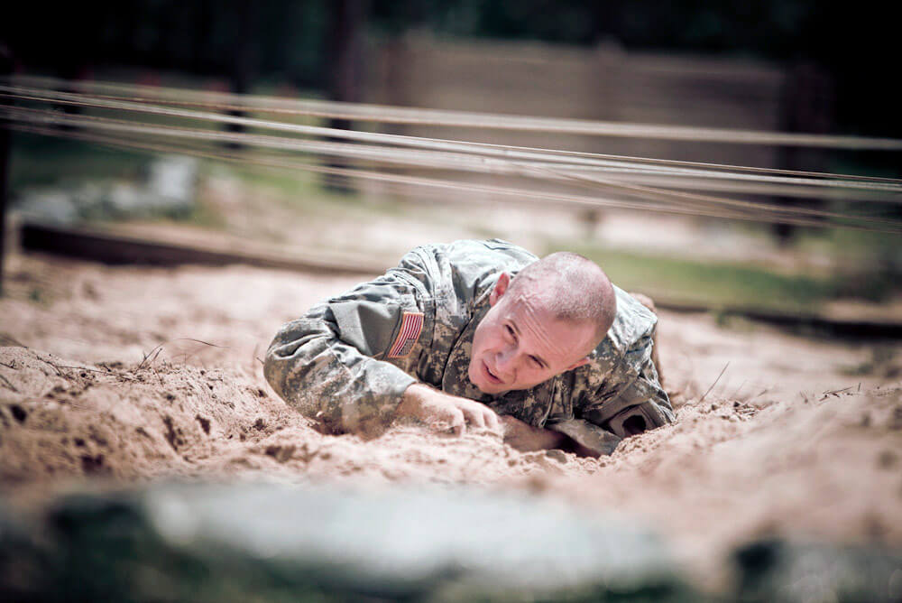 SSG Beau Detrick low crawls on the obstacle course during the 2012 National Guard Best Warrior Competition. Photo courtesy Illinois Army National Guard