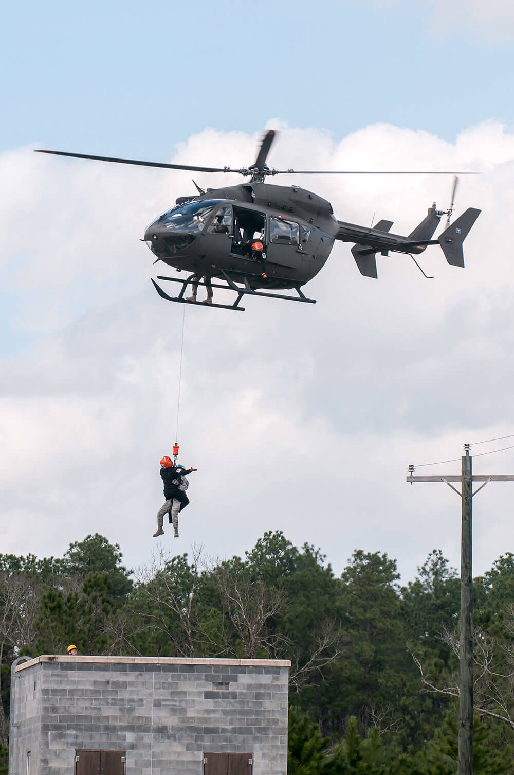 A South Carolina Army National Guard UH-72 Lakota helicopter crew hovers over buildings at the Combined Arms Combat Training Facility on Camp Shelby as members of the South Carolina Helicopter Aquatic Rescue Team hoist a simulated natural disaster victim from a rooftop during Patriot South 2018. Ohio National Guard photo by TSgt Nic Kuetemeyer