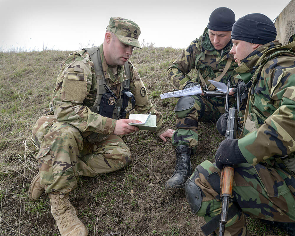 SSG Ada Boyer, assigned to 1st Squadron, 150th Cavalry Regiment, West Virginia Army National Guard, and Moldovan soldiers assigned to the 22nd Reconnaissance Battalion, verify coordinates while conducting a land navigation course during the Agile Hunter 2016. The overseas deployment training exercise is part of a multi-year DoD State Partnership Program. Army National Guard photo by SSG Brendan Stephens