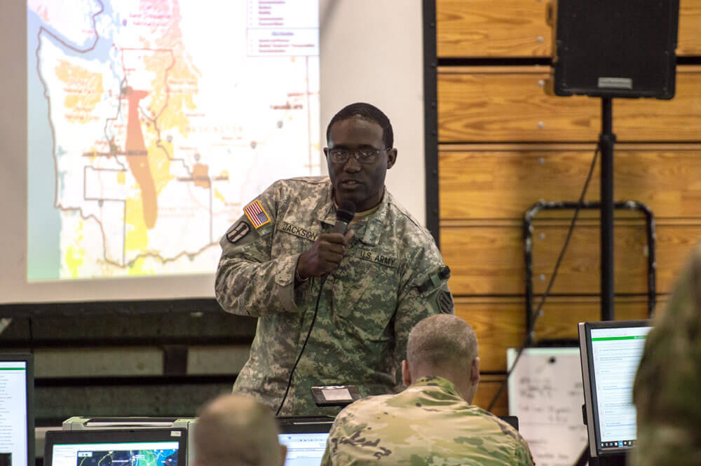An officer of the 46th Military Police Command, Michigan Army National Guard, relays updates regarding a fictional nuclear attack to the staff of the command center at Camp Atterbury, Ind., during the Vibrant Response training exercise, April 12, 2018. National Guard Bureau photo by Luke Sohl