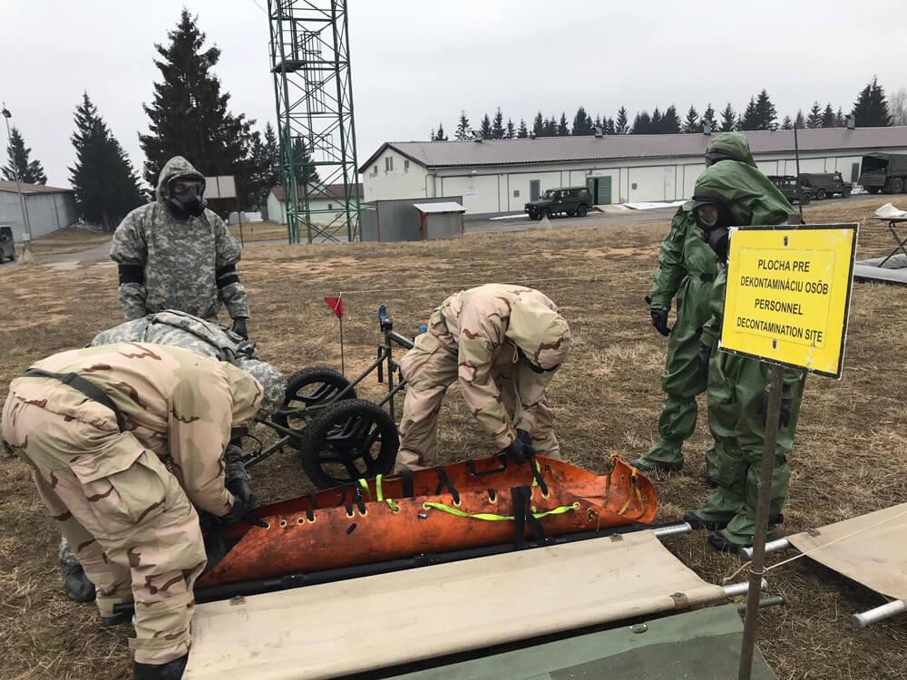 Donned in Mission Oriented Protective Posture (MOPP) suits, Indiana and Texas National Guard Soldiers work with members of the Czech Republic's CBRN Regiment during Operation Toxic Lance held in March 2018 at Training Area Lest in central Slovakia.