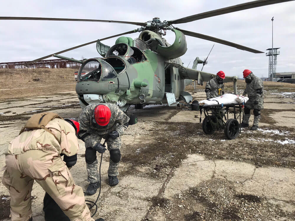 Indiana and Texas Army National Guard Soldiers load a fictional rescue victim onto a Slovakian military chopper during the scenario-based, chemical warfare training Operation Toxic Lance held in March 2018 at Training Area Lest in central Slovakia.