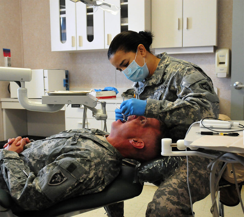 COL Michelle Conner, a dentist and clinic chief with the North Carolina Army National Guard Medical Detachment, performs a dental examination at Camp Butner, N.C. North Carolina Army National Guard photo by SGT Brian Godette