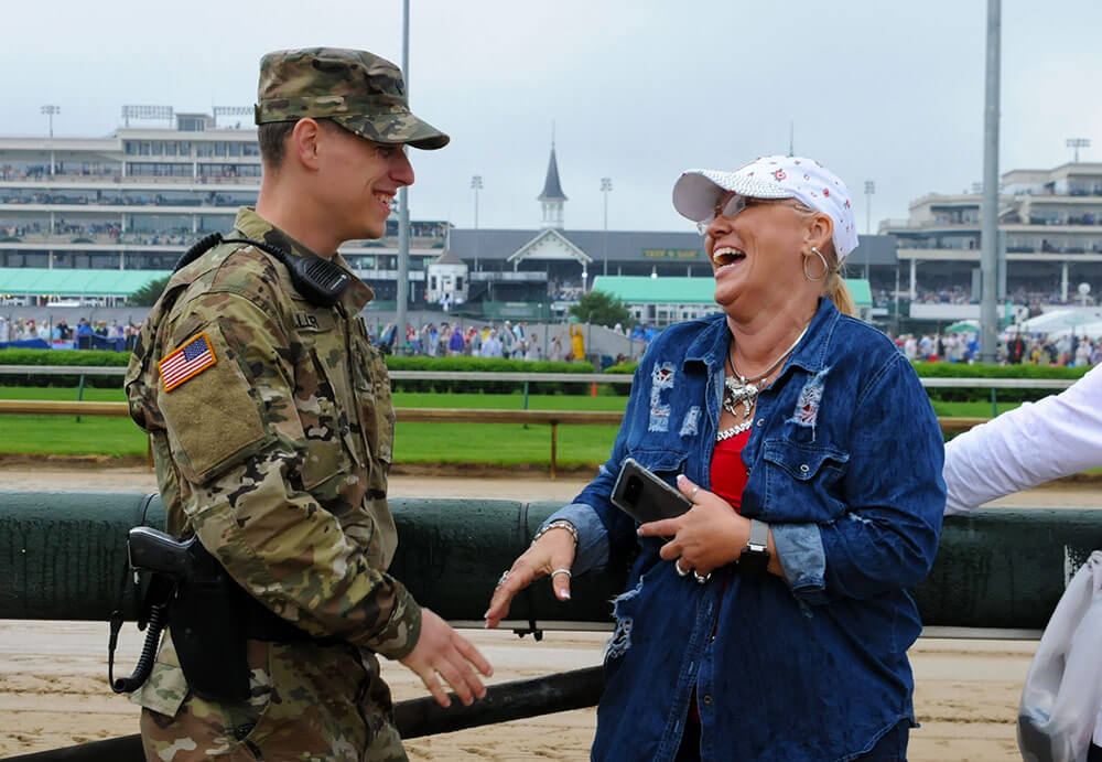 Kentucky Army National Guard Soldier, SPC Roy Miller, 617th Military Police Company, converses with an attendee of the 144th Kentucky Derby held at Churchill Downs, Louisville, Ky., this past May. Kentucky Army National Guard photo by SSG Benjamin Crane