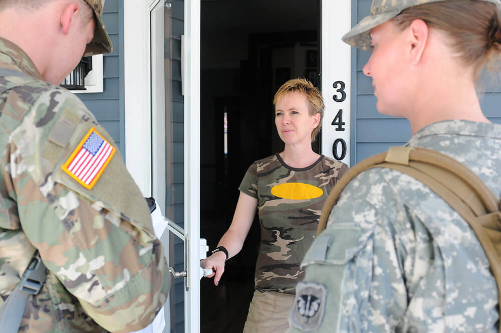 SPC Troy Sharpe (left) and SGT Sarah Pritzl, both with the 107th Maintenance Support Company, Wisconsin Army National Guard survey resident Heidi Kiley in the city of Omro, Wis., as part of a canvassing exercise during the Dark Sky training exercise. Wisconsin Army National Guard photo by SSG Matthew Ard