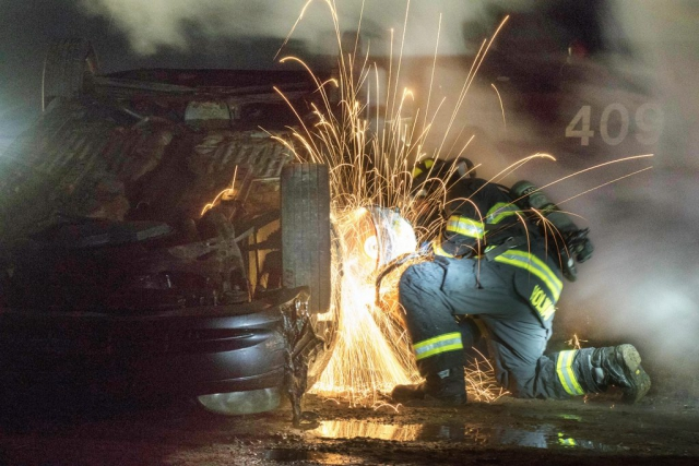 A Soldier with the 79th Engineer Company (Firefighting), Massachusetts Army National Guard, uses a circular saw to cut through a car door during a training exercise at Tactical Training Base Kelley on Joint Base Cape Cod, Mass. The training required Soldiers to ascertain the best method to evacuate dummies from a vehicle that was flipped and burning in the night. Massachusetts Army National Guard photo by PFC Sean Park