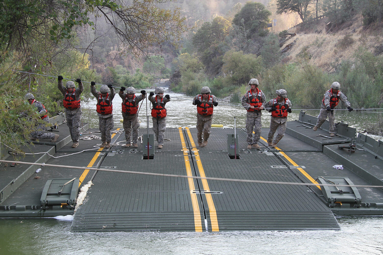 A launch and retrieve team from the 132nd Multirole Bridge Company (MRBC), 579th Engineer Battalion, 49th Military Police Brigade, California Army National Guard, uses a steel guideline to move a ramp-and-bay over Cache Creek River in Cache Creek Regional Park, Yolo County, Calif. The platforms are part of a floating bridge constructed by the MRBC to help California Department of Forestry and Fire Protection vehicles and equipment cross the river to battle wildfires. California Army National Guard photo by SSG Eddie Siguenza