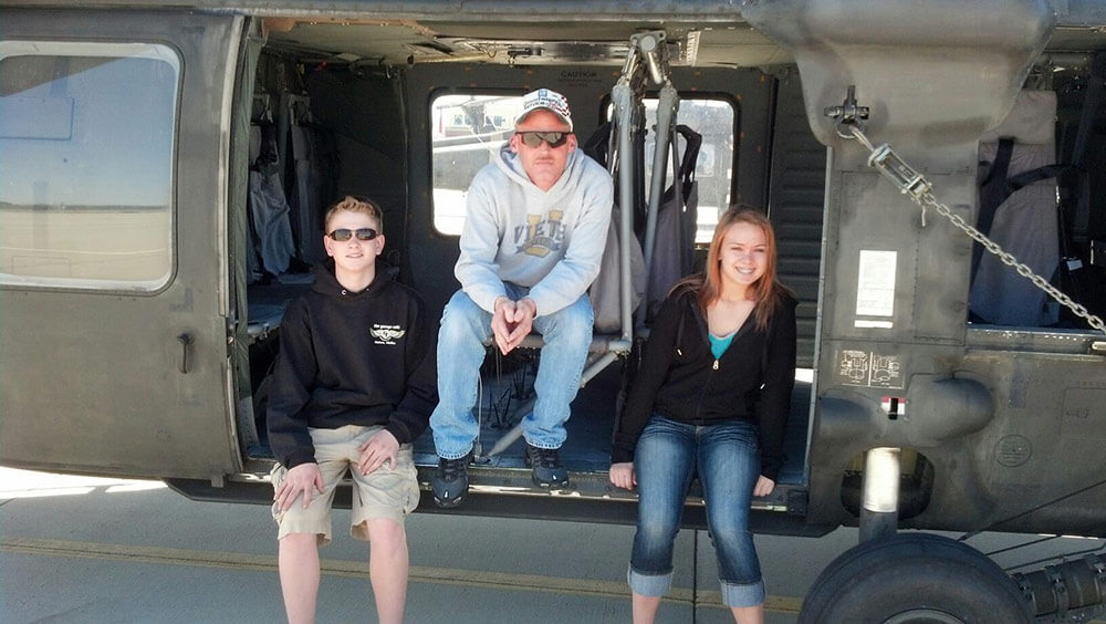 SSG Albert Vieth, shown with two civilians, Jacob Mills and Kendra Midkiff, after giving the two a tour of an Idaho National Guard military facility in 2013. Photo courtesy Jeff Mills