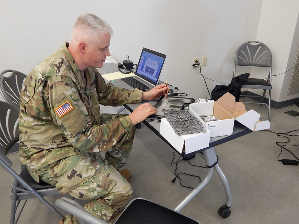 SSG Shawn Lane of the 3rd Information Operations Battalion, 124th Regional Training Institute, Vermont Army National Guard conducts a forensic investigation of a laptop during the 2018 Cyber Yankee network defense training event. New Hampshire Army National Guard photo by LTC Woody Groton