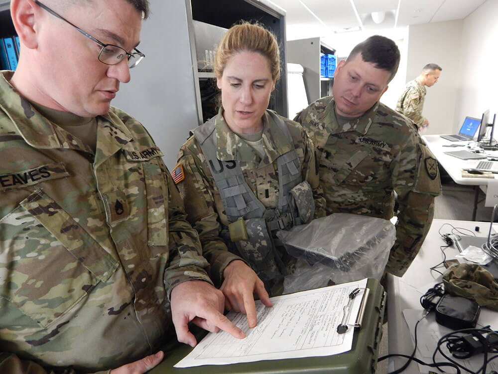 SSG Paul Eaves (left) and 1LT William Black (right), both of the 126th Cyber Protection Battalion, work with 1LT Heather Boucher of the 223rd Military Intelligence Battalion, Massachusetts National Guard, as they review a chain of custody for a locked laptop that was captured in a raid as part of a training scenario during Cyber Yankee 2018, a network defense training held in June of this year. New Hampshire Army National Guard photo by LTC Woody Groton