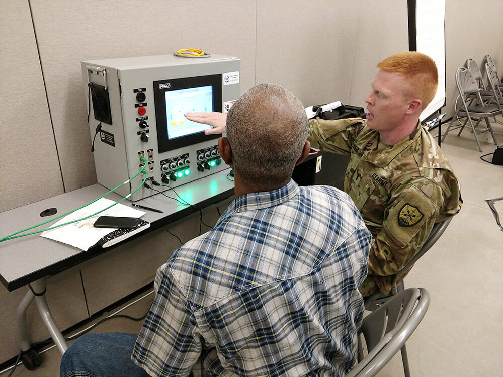 1LT Charles Mayer of the Virginia Army National Guard, 91st Cyber Brigade works with Norman Greene of the Massachusetts Water Resource Authority to analyze a fictional cyberattack on an industrial control systems/supervisory control and data acquisition (ICS/SCADA) system as part of 2018's Cyber Yankee exercise. New Hampshire Army National Guard photo by LTC Woody Groton