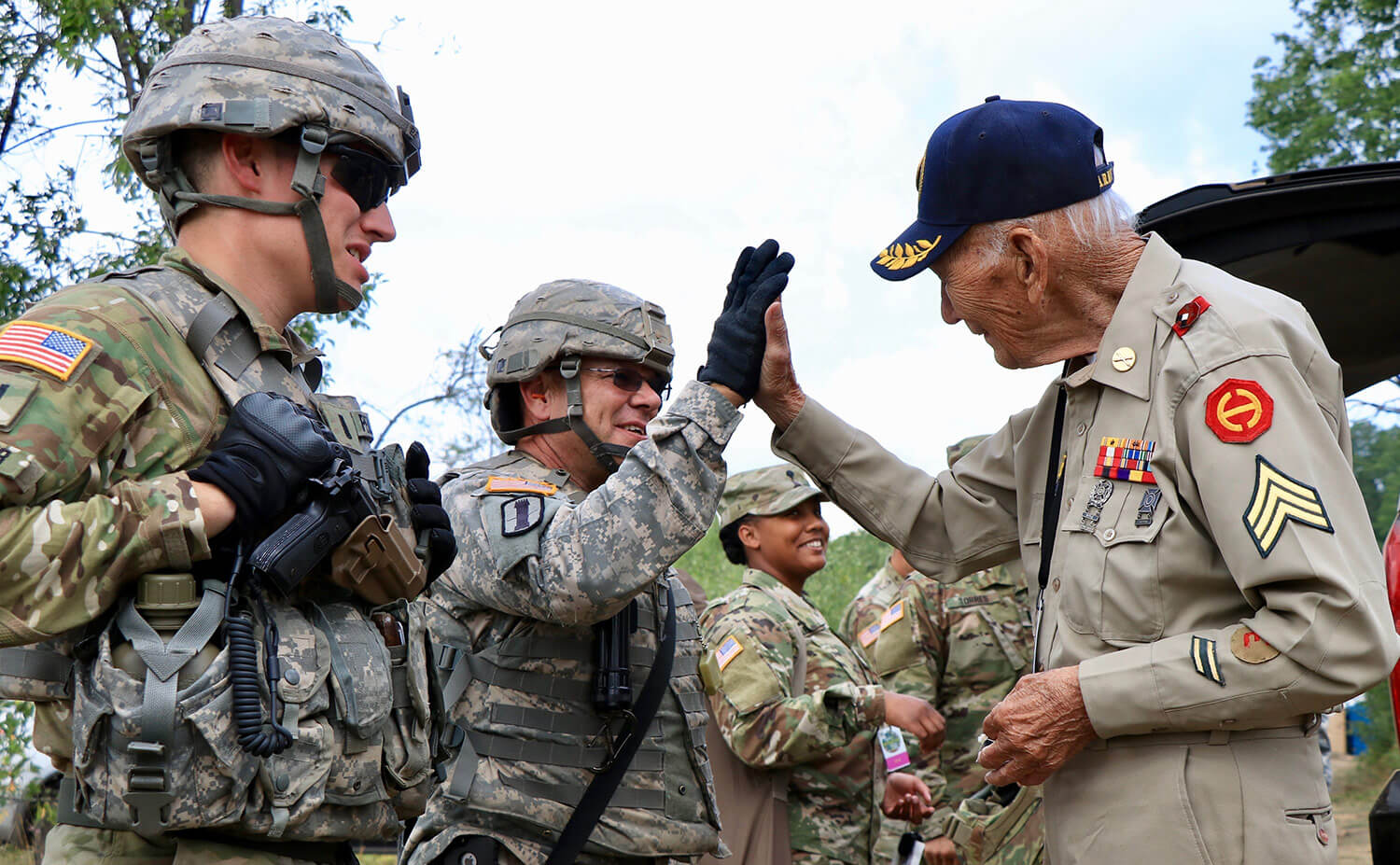 World War II Veteran Claude Cawood gives 1SG Jeffery Lemire, Battery A, 1st Battalion, 103rd Field Artillery Regiment, Rhode Island Army National Guard, a high-five after firing the M777 Howitzer this past August at Camp Grayling, Mich. Cawood, who served three years in the Philippines and was a former section chief on the M105 Howitzer, took the opportunity to visit Soldiers supporting the Northern Strike 2018 exercise. Iowa Army National Guard photo by 1SG Sara Robinson