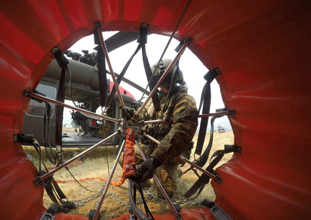 SSG Ge Xiong, UH-66 Black Hawk crew chief for the California Army National Guard's Alpha Company, 1106th Theatre Aviation Support Maintenance Group, checks his 600-gallon water bucket prior to a mission in the summer of 2018 battling the Mendocino Complex Fires in Lake, Colusa and Mendocino counties, Calif. California Army National Guard pilots used helicopters to drop close to a half-million gallons of water in just over a week as the Ranch and River fires combined to become California's largest wildfire in State history. California Army National Guard photo by SSG Eddie Siguenza