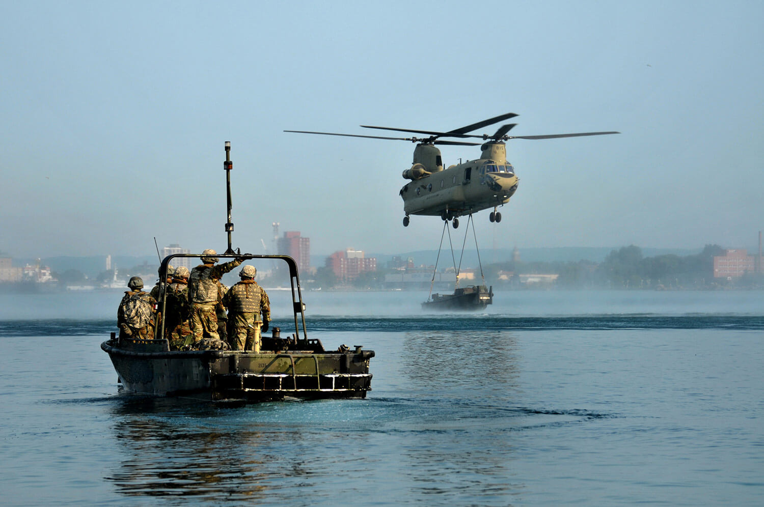 Engineers from Michigan Army National Guard's 1437th Multi-Role Bridge Company, based out of Sault Saint Marie, Mich., wait as a Chinook from B Company, 3rd Battalion, 238th Aviation Regiment, based out of Grand Ledge, Mich., makes an aerial delivery of sling loaded components for an improved float bridge, also known as a ribbon bridge, on the St. Mary's River. The Soldiers of the 1437th, working from 500-hp MK-II Bridge Erection Boats, maneuvered the separate pieces to rehearse the assembling of a sturdy floating bridge during a training scenario in August of this year. Michigan Army National Guard photo by SFC Helen Miller