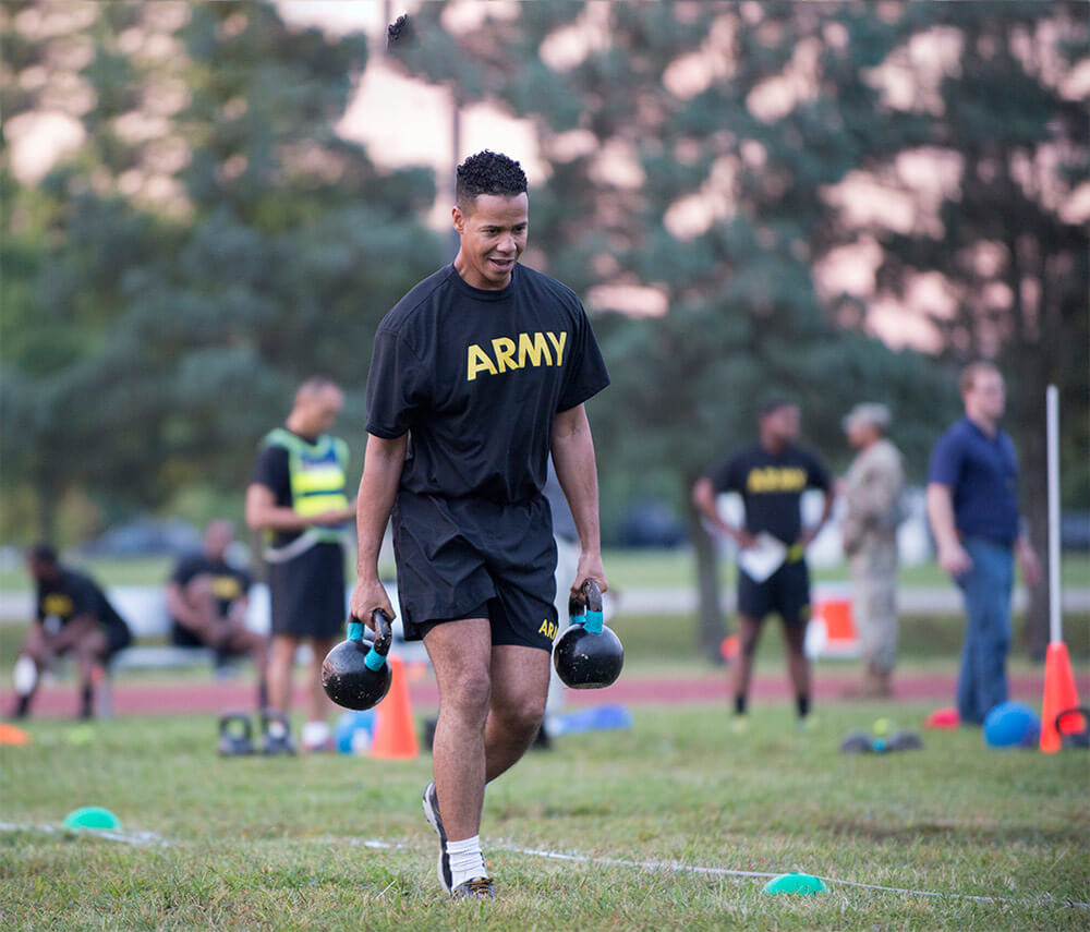 A Soldier carries two 40-pound kettlebell weights during a pilot for the new Army Combat Fitness Test. U.S. Army photo by Sean Kimmons