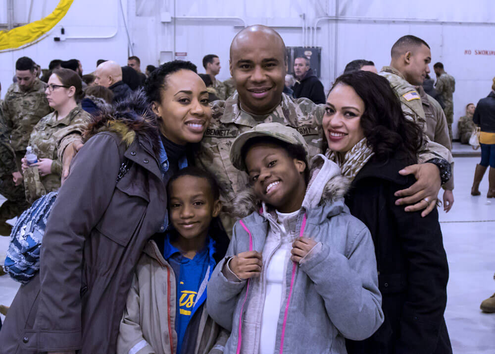 SGT Gary Bennett, 101st Expeditionary Signal Battalion, poses with his Family following the unit's farewell ceremony at Stewart Air National Guard Base, March, 2018. Approximately 300 members of the battalion departed for further mobilization training at Fort Hood, Texas, before heading overseas in support of Operation Inherent Resolve. New York Army National Guard photo by SGT Jeremy Bratt