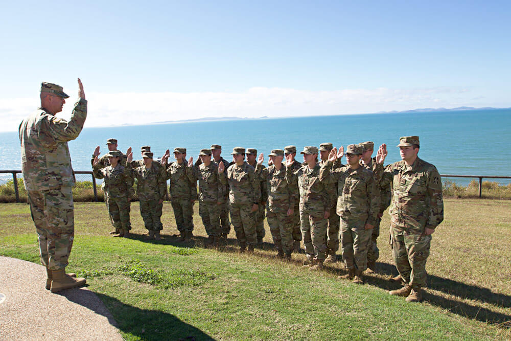 Members of Indiana's 76th Infantry Brigade Combat Team raise their right hands as their brigade commander, COL Robert Burke, leads them through a once-in-a-lifetime reenlistment ceremony held July 2018 in Yeppoon, Australia, while the unit was deployed to participate in the annual multilateral training, Exercise Hamel. Indiana Army National Guard photo by SPC Joshua Syberg