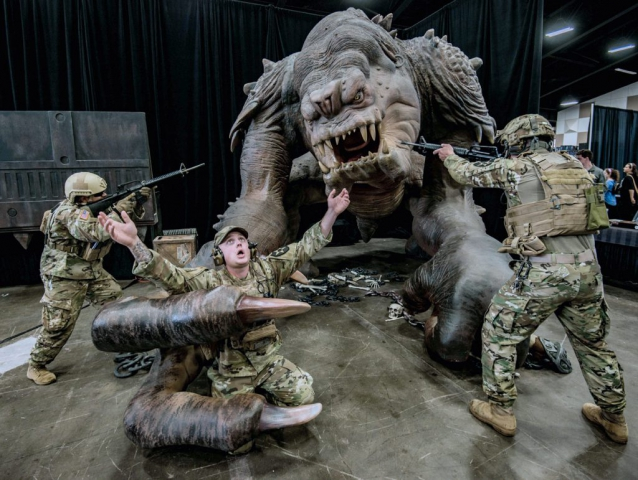 Members of Alpha Company, 1st Battalion, 161st Infantry Regiment, SPC Marco Mayorquin (left) and 1LT Casey Thometz (right), mock-fight a rancor in order to save SGT Brandon Gray as part of a spoof at the 2018 Washington State Toy and Geek Fest in Puyallup, Wash. Washington Army National Guard photo by SGT David Carnahan