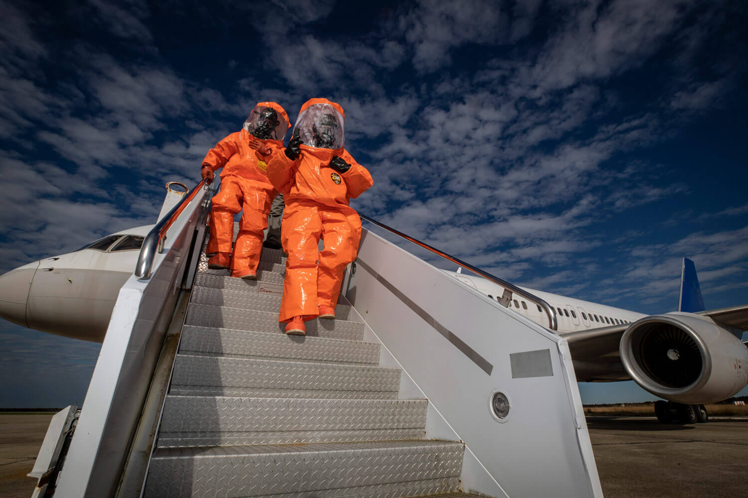 SGTs Mauricio Caceres and Cory Sweetman descend down air-stairs from an aircraft being used as part of a chemical, biological, radiological and nuclear defense exercise held at Atlantic City International Airport, N.J., in November of 2018. SGT Caceres and SGT Sweetman are with the 21st Weapons of Mass Destruction-Civil Support Team (21st WMD-CST), New Jersey National Guard. New Jersey National Guard photo by MSgt Matt Hecht