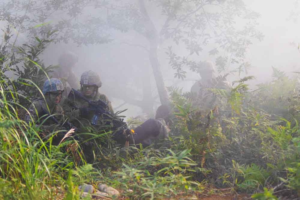 Soldiers of the Indiana National Guard's 76th Infantry Brigade Combat Team move through smoke at Ojojihara Maneuver Area, Japan, during a mock assault as part of Exercise Orient Shield 2018, an annual, bilateral field-training exercise co-hosted by U.S. Army Pacific Command and the Japan Ground Self-Defense Force.